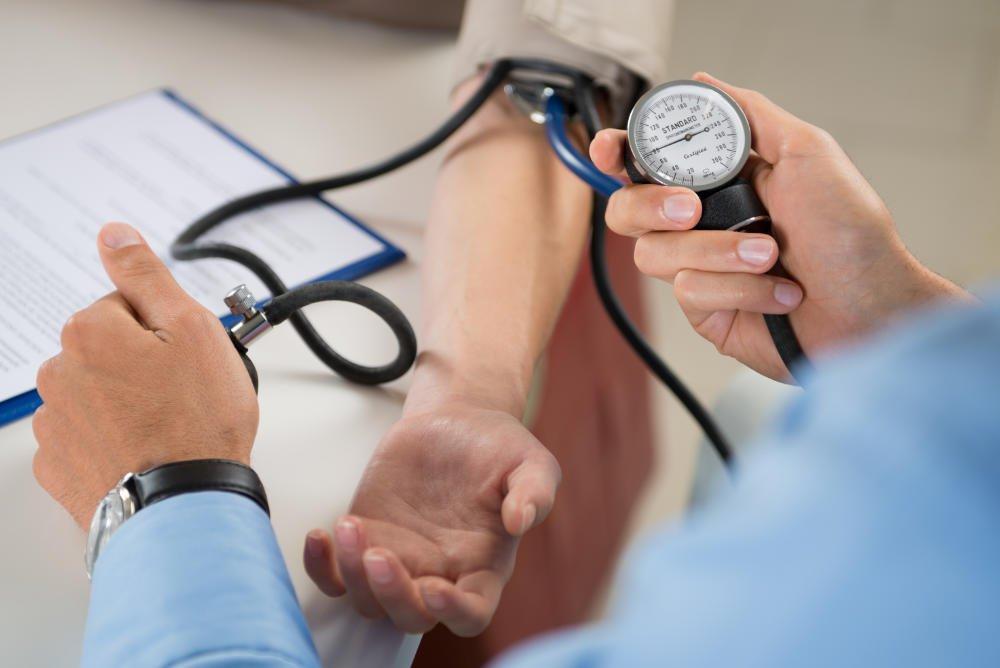Doctor measures blood pressure In patient
